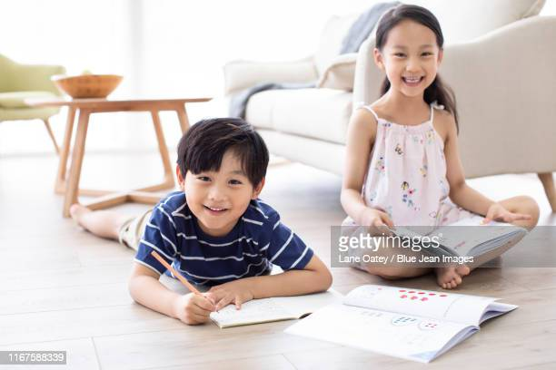 happy chinese sibling studying in living room - workbook stock pictures, royalty-free photos & images