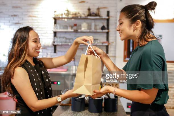 happy chinese woman receiving takeaway - passing giving stock pictures, royalty-free photos & images