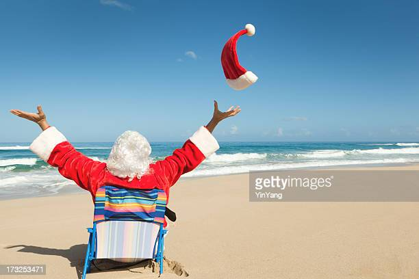 happy christmas santa claus sitting on beach, enjoying tropical vacation - hawaii christmas stock pictures, royalty-free photos & images