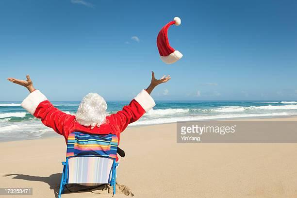 noël père noël assis sur la plage, profitant de vacances sous les tropiques - pere noel humour photos et images de collection