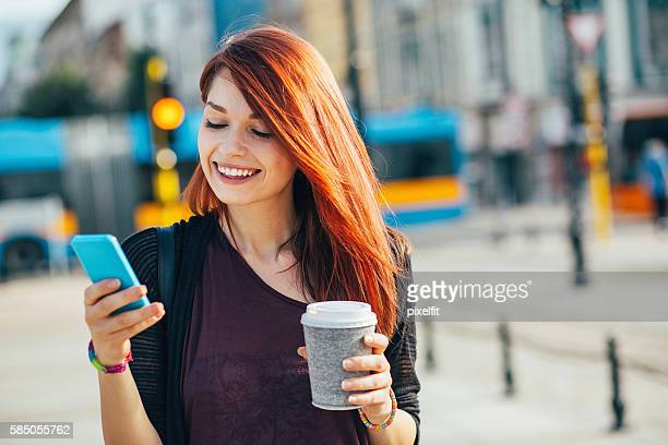 happy city girl texting on the street - dyed red hair stock pictures, royalty-free photos & images