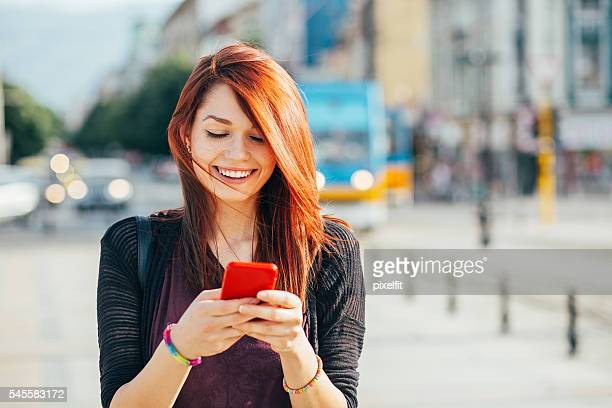 happy city girl texting - redhead girl stock photos and pictures