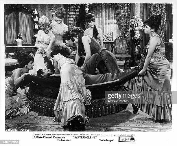 A happy Claude Akins is surrounded by women of brothel in a scene from the stage play 'Waterhole' 1967
