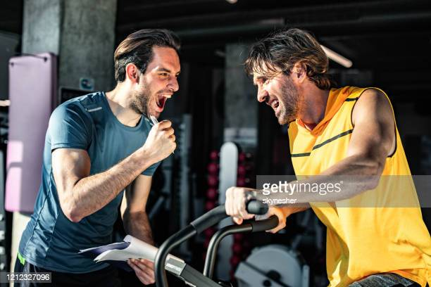 happy coach cheering for athletic man on stationary bike in a gym. - spinning stock pictures, royalty-free photos & images