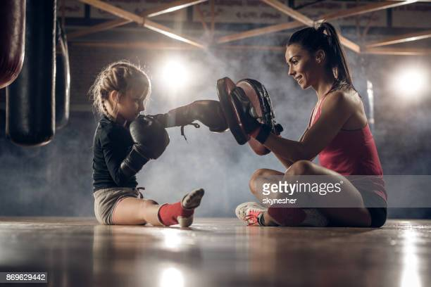 happy coach exercising boxing punches with little girl on a floor in a health club. - artes marciais imagens e fotografias de stock