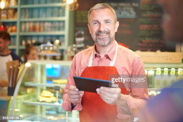 happy coffee shop owner with tablet