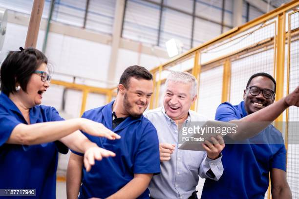 happy colleagues celebrating and dancing in industry - down syndrome stock pictures, royalty-free photos & images