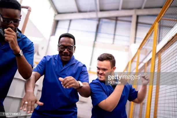 gelukkige collega's vieren en dansen in de industrie - friday stockfoto's en -beelden