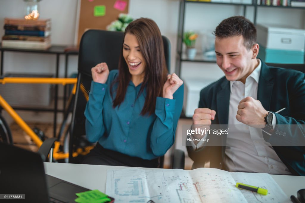 Happy colleagues cheering for good results : Stock Photo