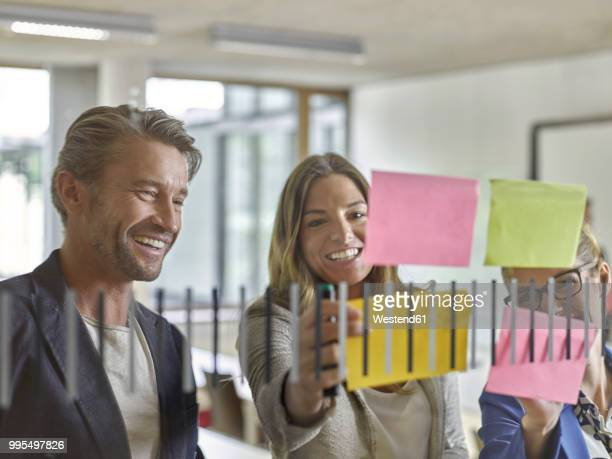 happy colleagues discussing with sticky notes at glass pane - werkstatt stock-fotos und bilder