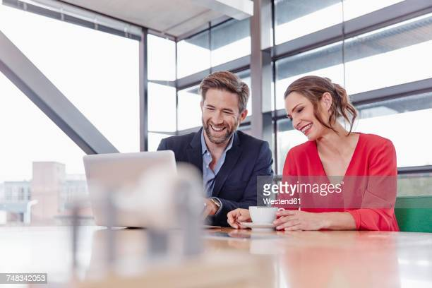 happy colleagues in office sharing laptop - caffè bevanda foto e immagini stock
