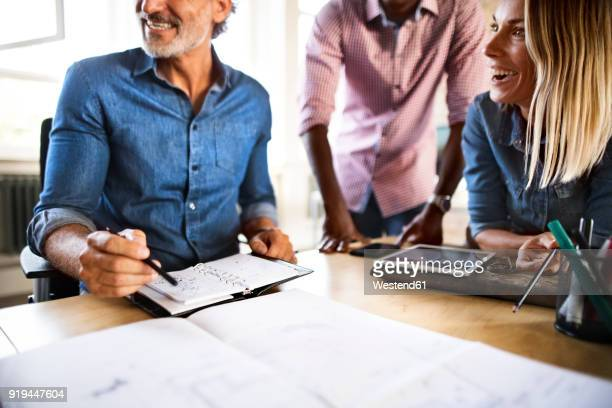 Happy colleagues with plan at desk in office