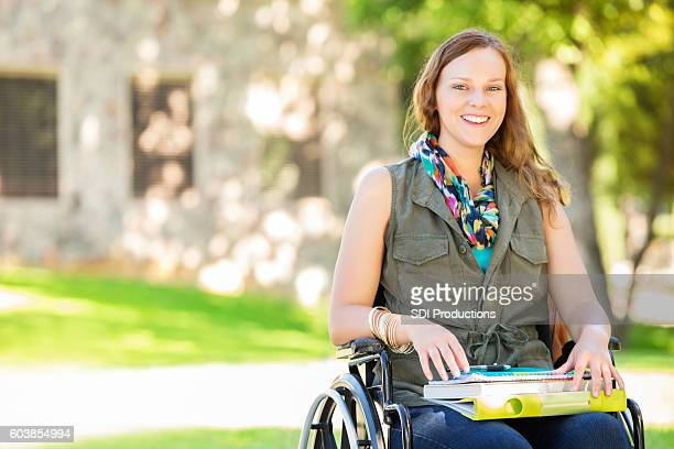 Happy college girl in wheelchair on campus