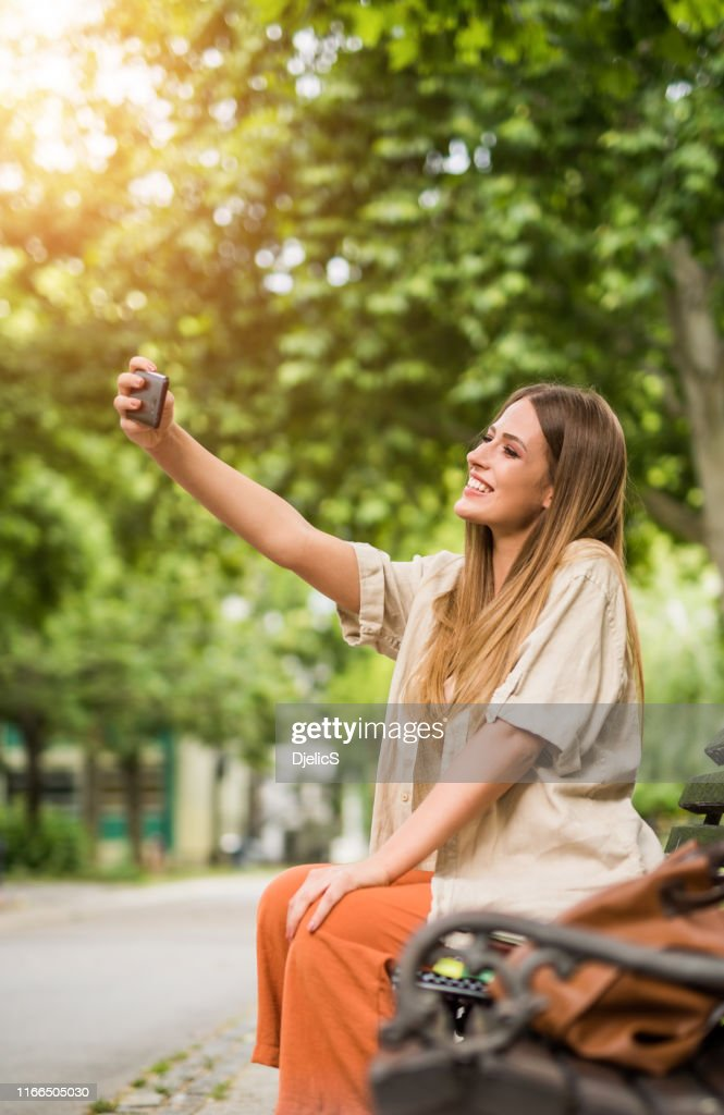 Happy college girl taking a selfie in the park. : Stock Photo