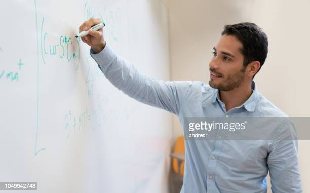 happy college student in class writing on the board - mathematics stock pictures, royalty-free photos & images