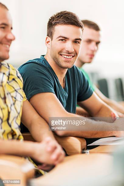 Happy college student in classroom looking at camera.