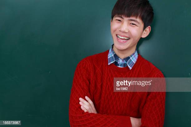happy college student in front of blackboard