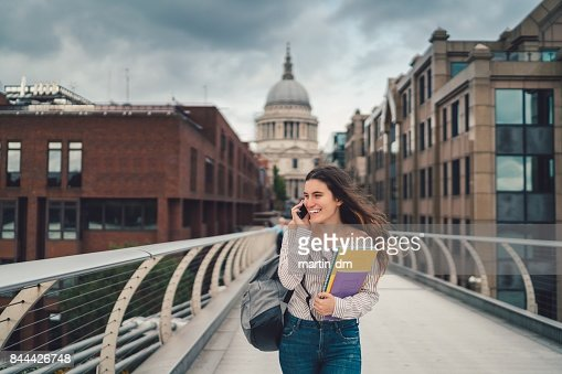Happy college student in London using phone