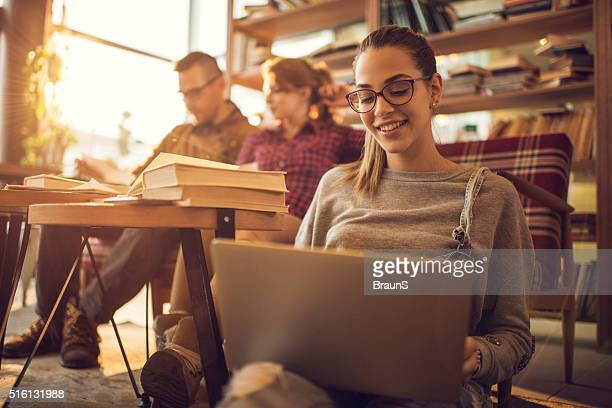 Faculdade estudante feliz, navegar na Internet em seu computador portátil.