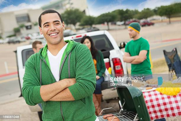 Happy college student tailgating with friends near football stadium
