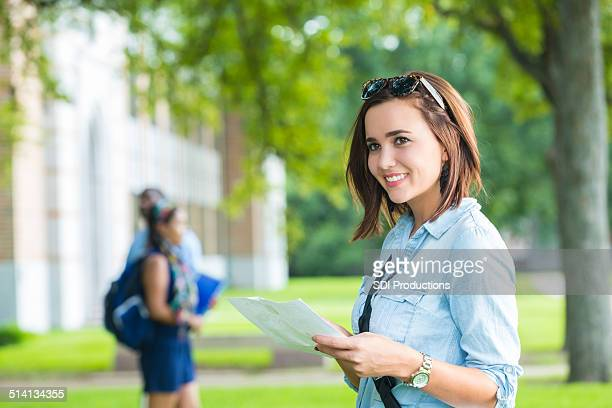 Happy college student using campus man while walking to class