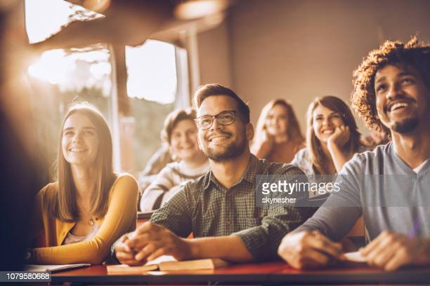 happy college students listening to a lecturer in the classroom. - lecture hall stock pictures, royalty-free photos & images
