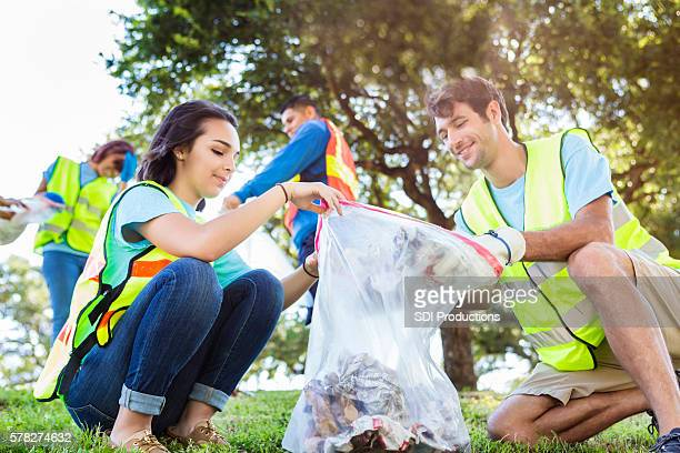 happy community service people cleaning up the park - picking up stock photos and pictures