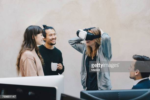 Happy computer programmer wearing VR glasses while talking to colleagues in office