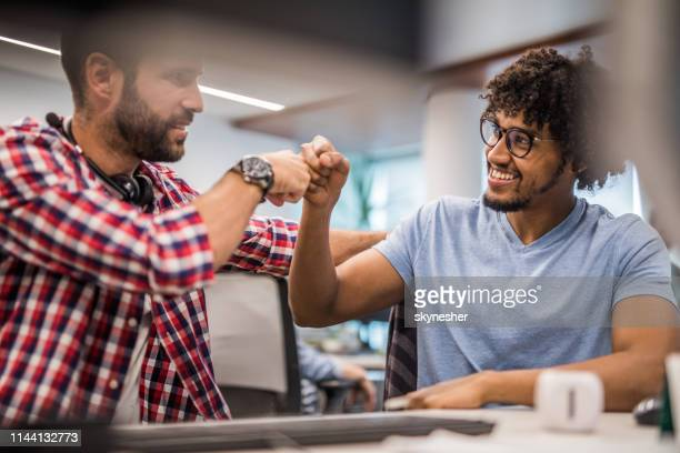 happy computer programmers giving each other fist bump in the office. - fist bump stock pictures, royalty-free photos & images