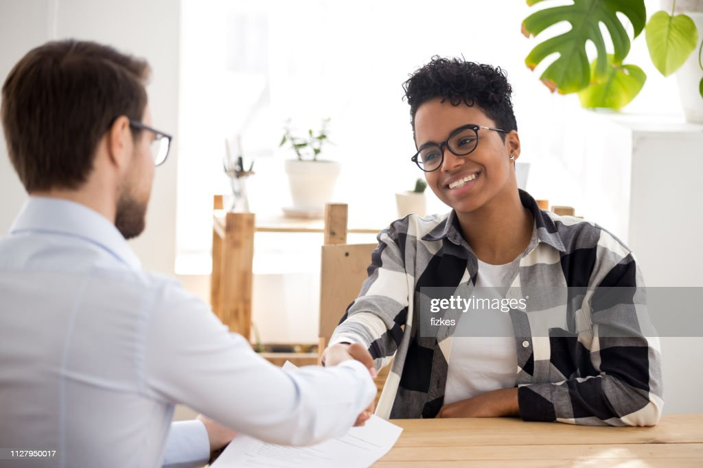 Happy confident african applicant shaking hand of hr getting hired : Stock Photo