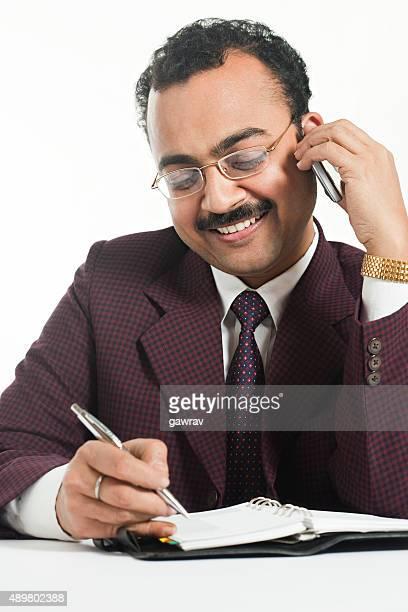 Happy zuversichtlich Geschäftsmann bei seiner Arbeit und spricht am Telefon.