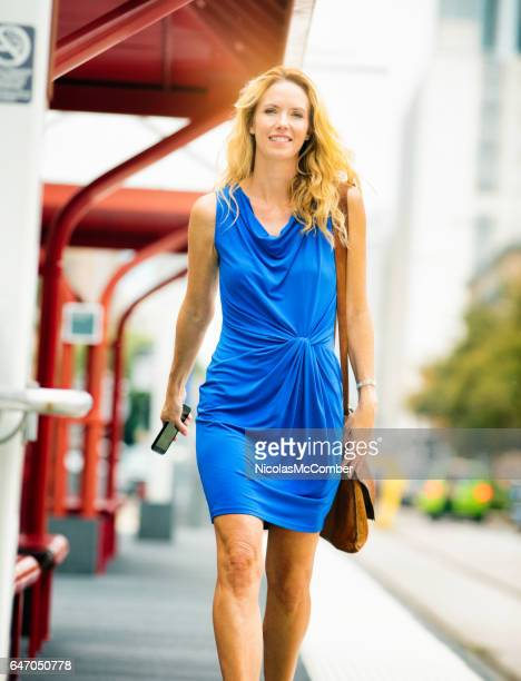 Happy Confident Mature female in blue dress walking phone in hand