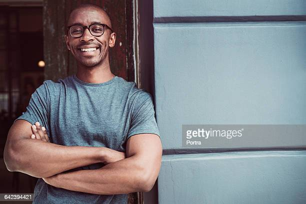happy confident professional leaning on wall - arms crossed stock pictures, royalty-free photos & images