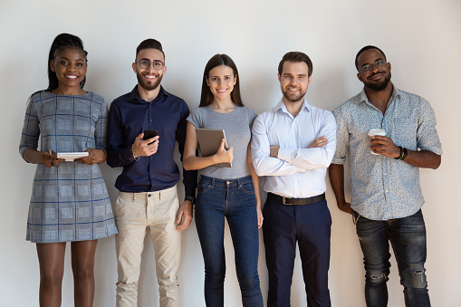 Happy confident successful multiethnic workers standing near wall. 1185220779