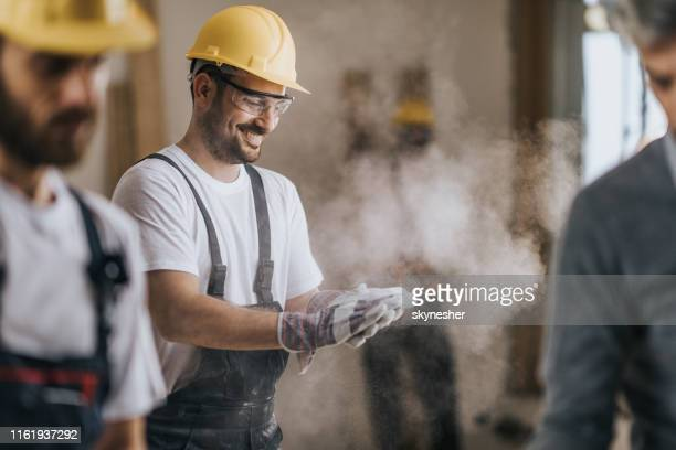 happy construction worker cleaning his gloves from sawdust at in renovating apartment. - built structure stock pictures, royalty-free photos & images