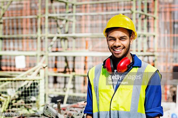 Happy construction worker standing at site