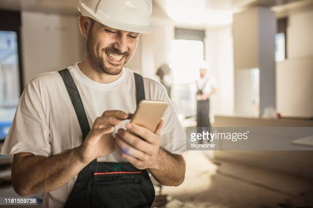 happy construction worker using cell phone during home renovation. - building contractor stock pictures, royalty-free photos & images