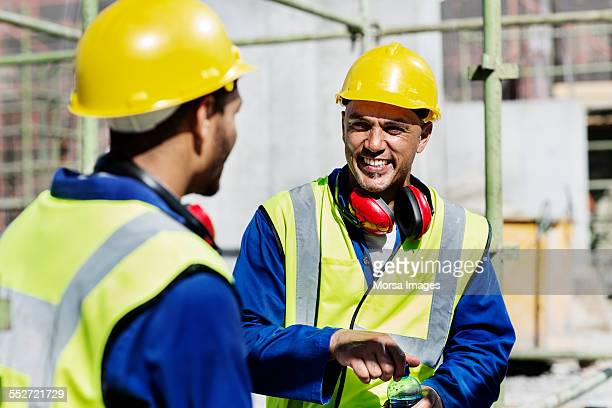 Happy construction workers talking at site