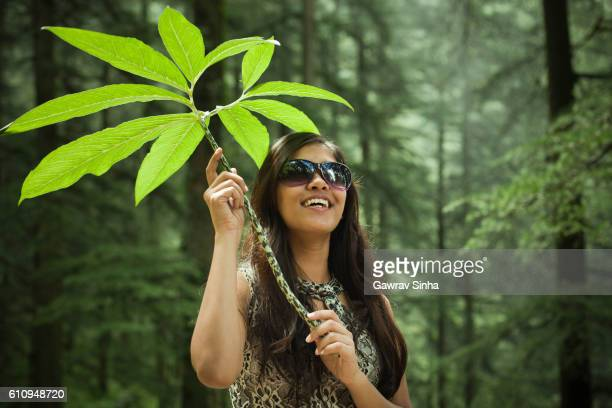 Happy cool girl in nature holding plant and looking up.