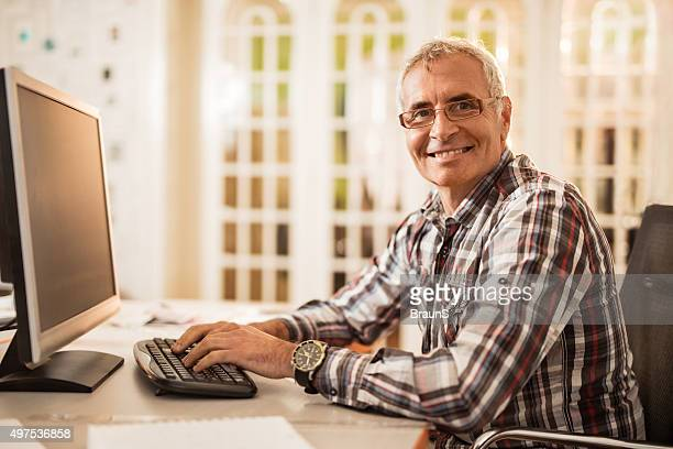 Happy corporate businessman working on desktop PC in the office.