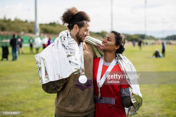 happy couple admiring each other after stampede race - medallist stock pictures, royalty-free photos & images