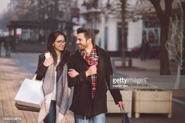 happy couple after shopping on black friday sale - black friday stock pictures, royalty-free photos & images