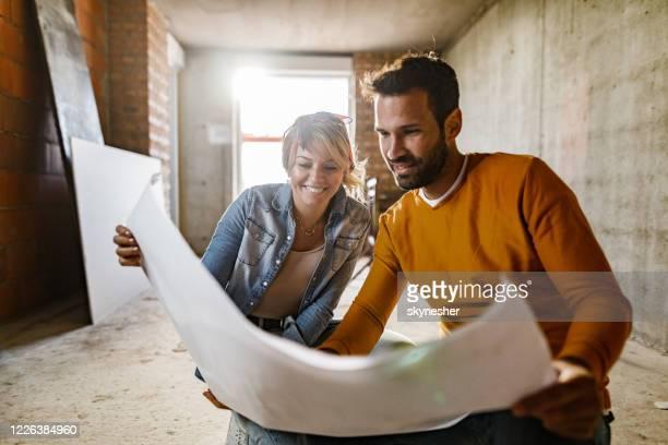 gelukkig paar analyseren plannen in hun renoveren appartement. - herbouwen stockfoto's en -beelden