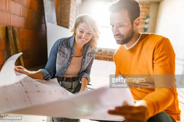 happy couple analyzing plans at their renovating apartment. - renovation stock pictures, royalty-free photos & images
