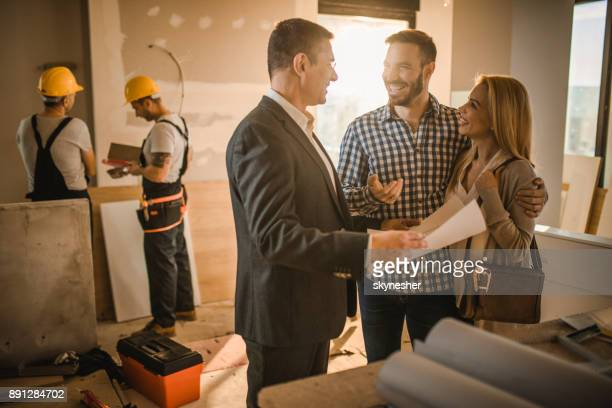 happy couple and building contractor talking about housing plan at construction site. - reform stock pictures, royalty-free photos & images