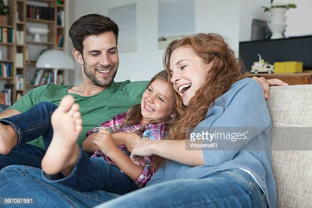 Happy couple and little daughter on the couch at home