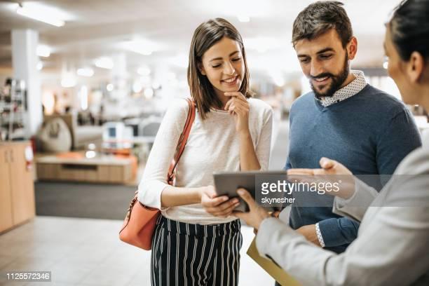 couple heureux et vendeuse au magasin de meubles à l'aide de touchpad. - client photos et images de collection