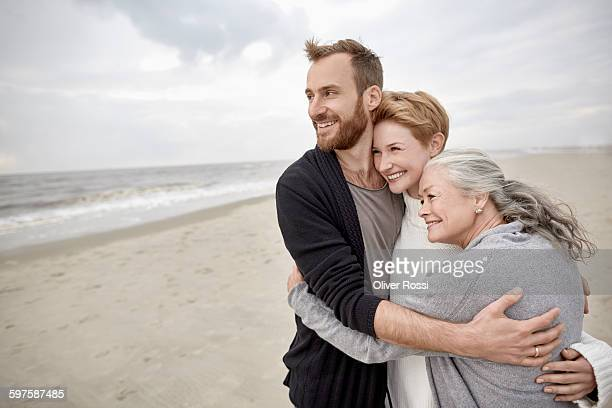 Happy couple and senior mother hugging on beach