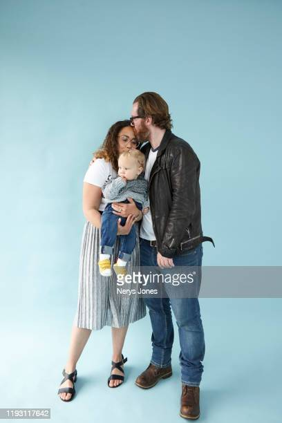 happy couple and their baby against pale blue background - nerys jones stock photos and pictures