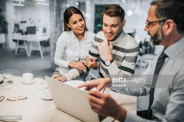glückliches paar und ihr finanzberater mit laptop im büro. - versicherung stock-fotos und bilder